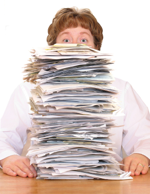 A project manager wades behind a stack of standard forms.
